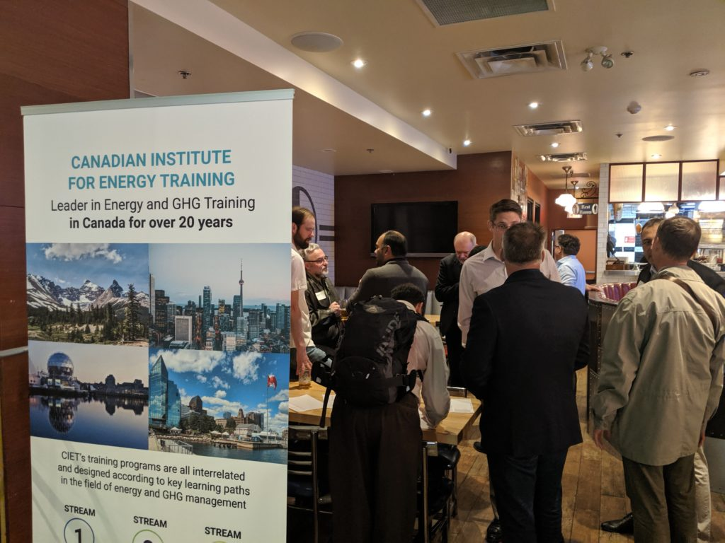 A group of people standing and talking at a restaurant behind a Canadian Institute for Energy Training banner sign
