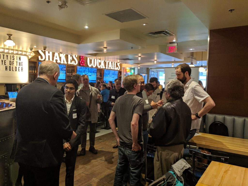 A group of people standing and talking at a restaurant in front of bright signs